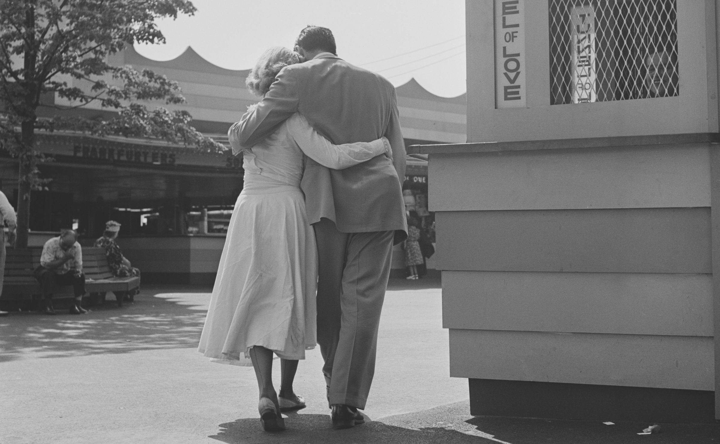 A couple walk toward a Tunnel Of Love with their arms around each other's waists.