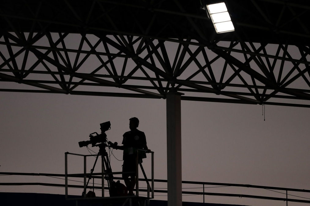 a camera operator is silhouetted by a dusk sky