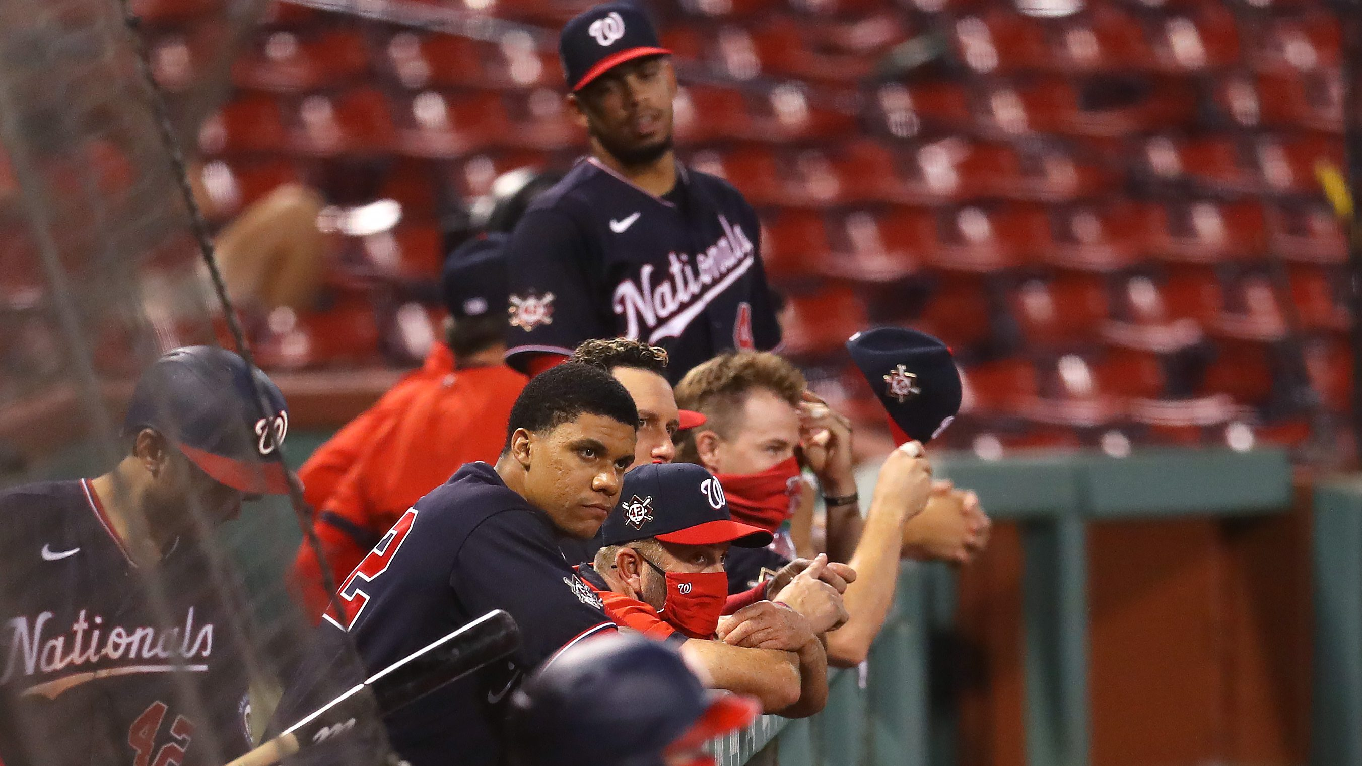 Washington Nationals players lean over the dugout railing during a game against the Boston Red Sox.