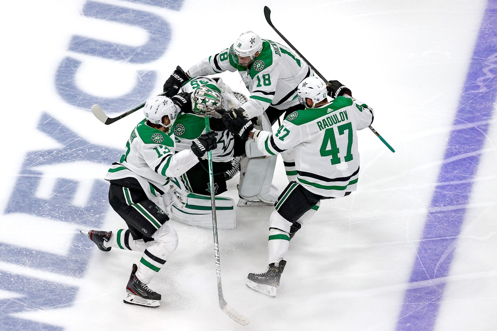 Jason Dickinson #18, Alexander Radulov #47 and Mattias Janmark #13 of the Dallas Stars grab on to Anton Khudobin #35 as they celebrate their 3-2 overtime victory against the Vegas Golden Knights to win Game Five of the Western Conference Final