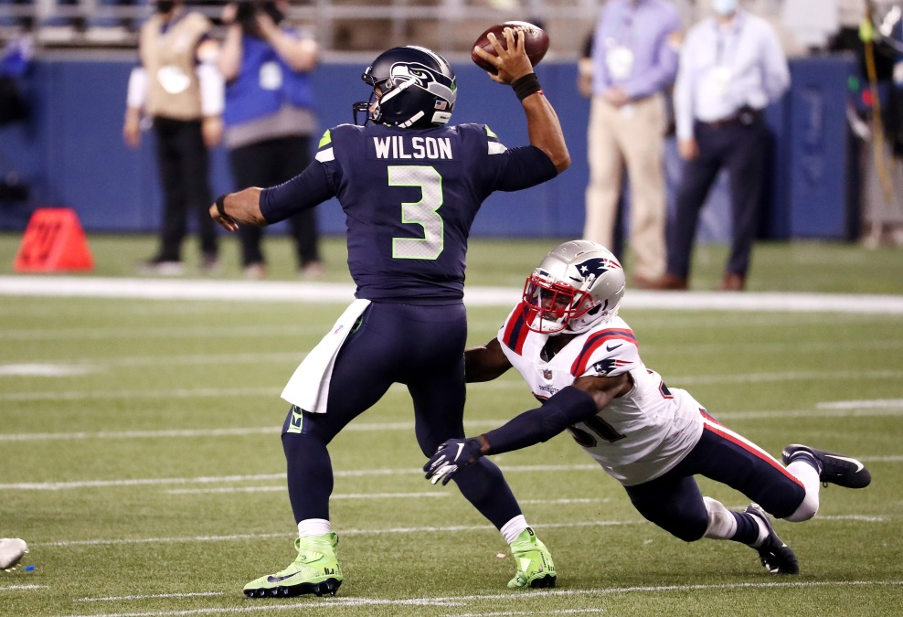 Jonathan Jones #31 of the New England Patriots attempts to tackle Russell Wilson #3 of the Seattle Seahawks