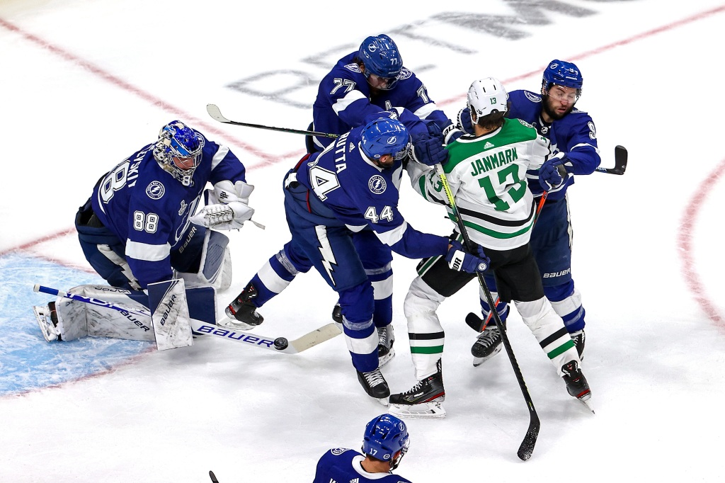 Mattias Janmark #13 of the Dallas Stars is checked by Victor Hedman #77 and Tyler Johnson #9 of the Tampa Bay Lightning