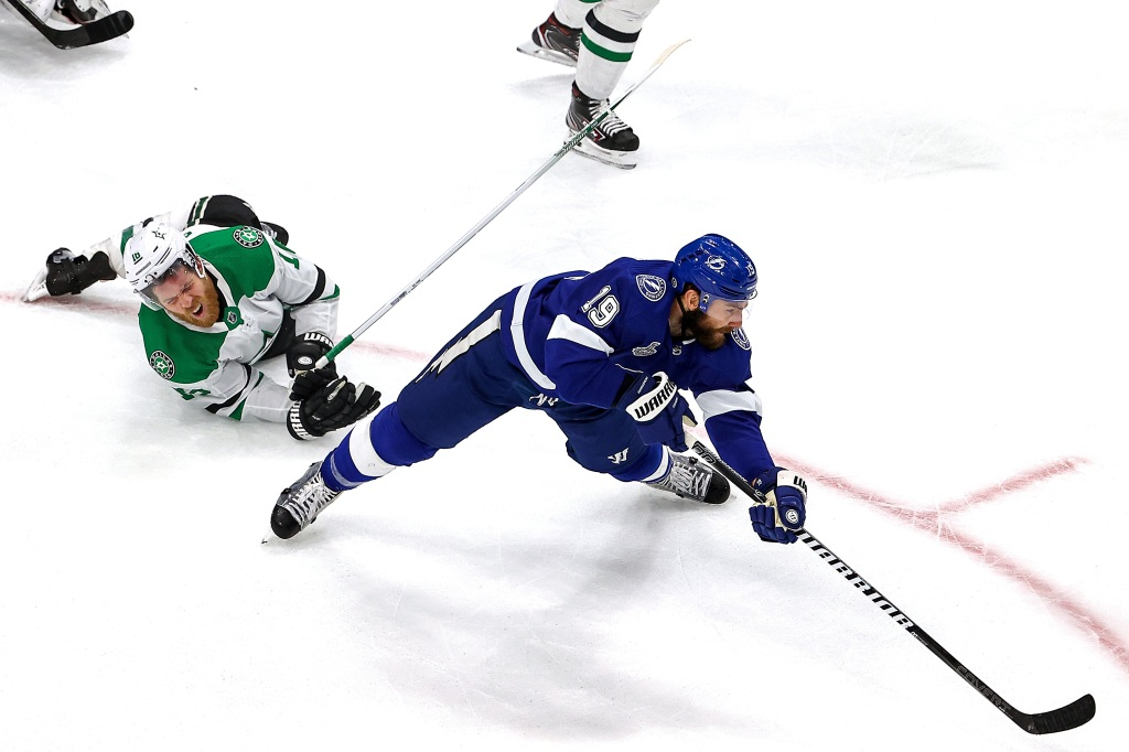Joe Pavelski #16 of the Dallas Stars gets tripped up against Barclay Goodrow #19 of the Tampa Bay Lightning