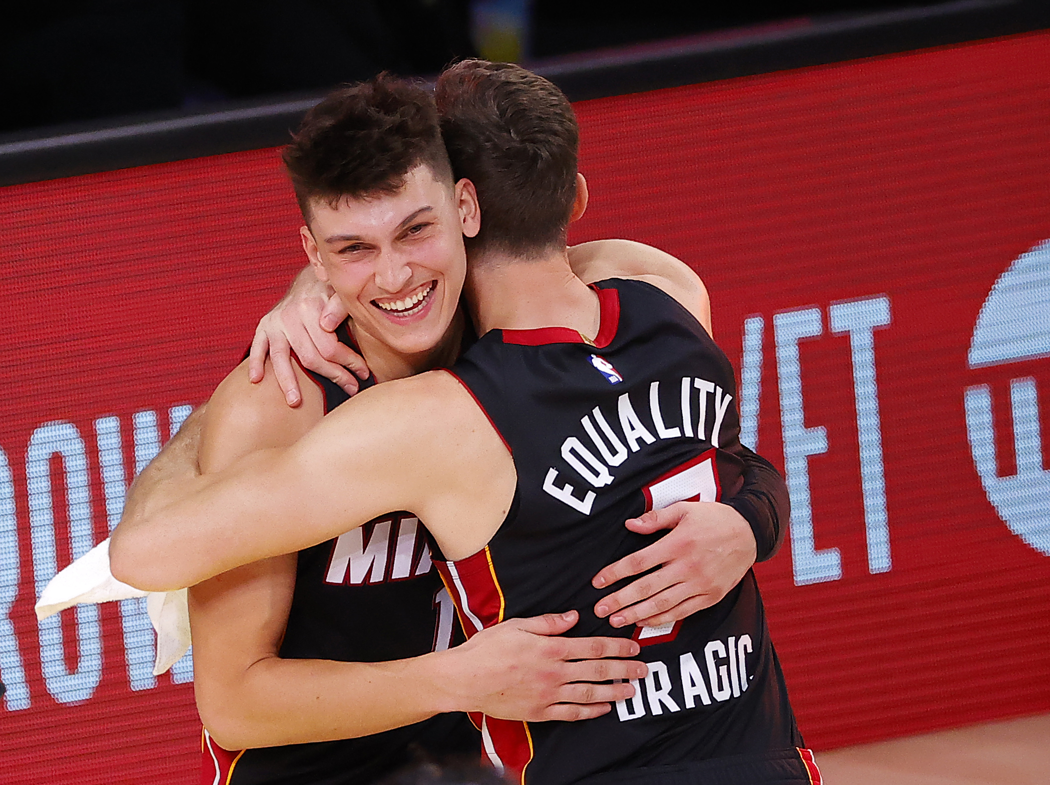Tyler Herro #14 of the Miami Heat and Goran Dragic #7 of the Miami Heat react after their win over the Boston Celtics in Game Four of the Eastern Conference Finals.
