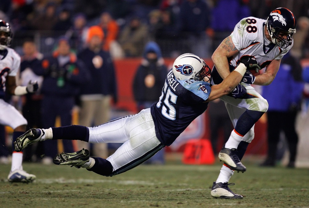 A player on the denver broncos grips the football at his hip while a player on the titans stretches airborn to try and strip it.