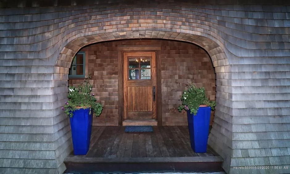 a wooden door with two blue planters on either side sits tucked inside a curved entryway