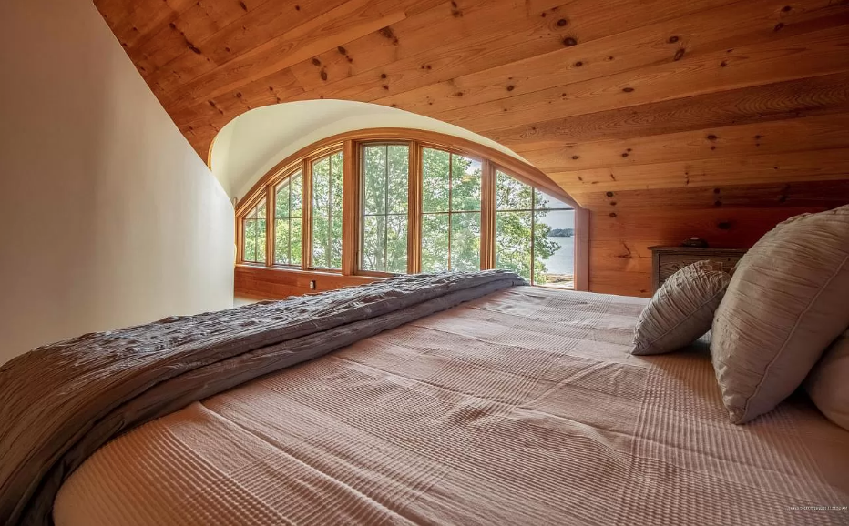 a curved window nestled inside a wooden wall