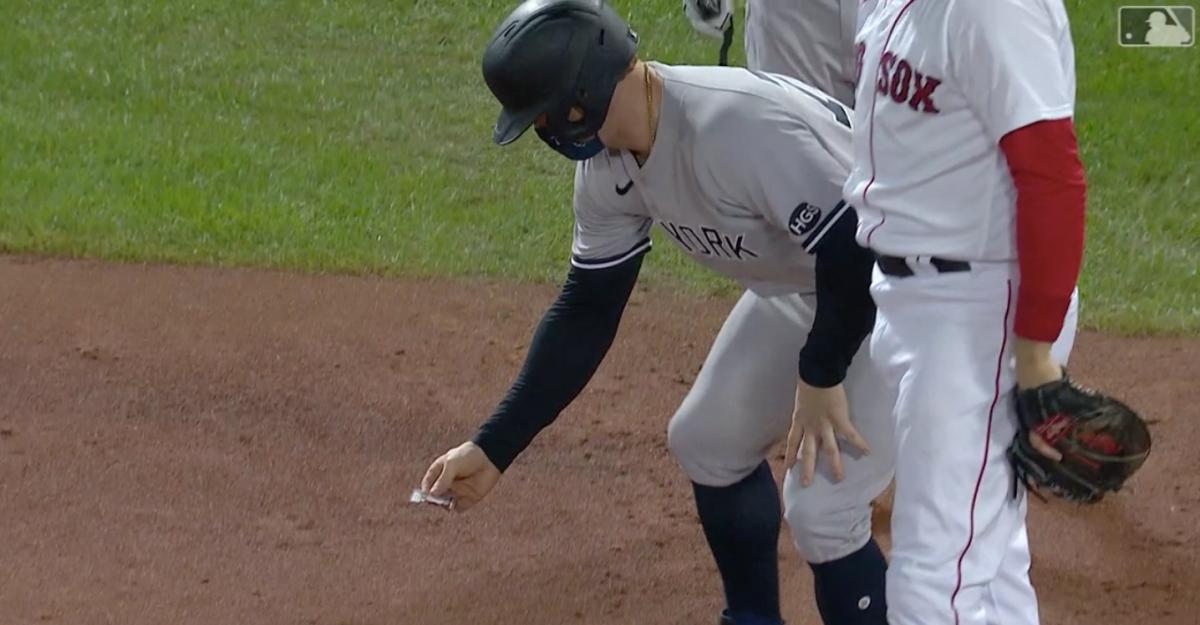 Yankees player Clint Frazier aids a bug on the infield dirt.