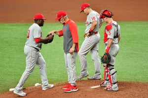 Phillies manager Joe Girardi takes the ball from reliever Hector Neris as first baseman JT Realmuto and catcher Andrew Knapp look on. They all look dejected.