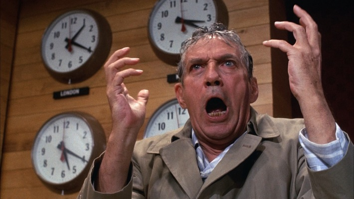 Howard Beale from the film Network, angry in front of clocks.