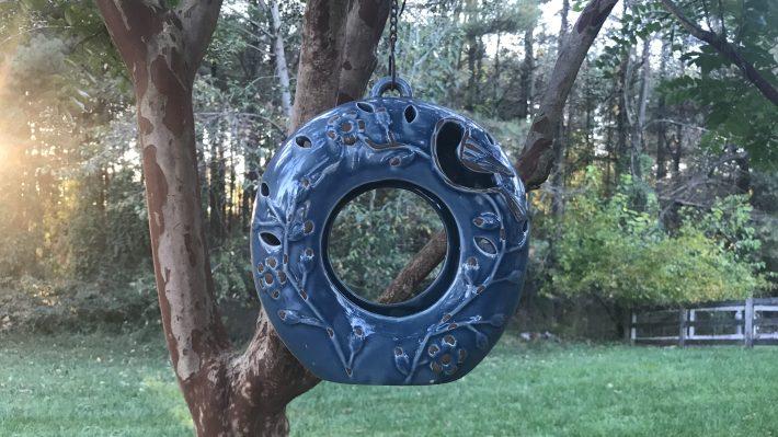 A blue ceramic bird-feeder.