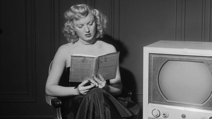 Actress Dagmar reads book beside TV in old black and white photo