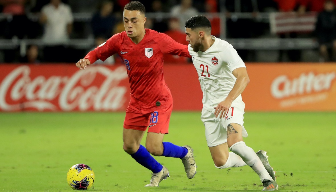 Sergino Dest #18 of the United States drives against Jonathan Osorio #21 of Canada during the CONCACAF Nations League match at Exploria Stadium on November 15, 2019 in Orlando, Florida.
