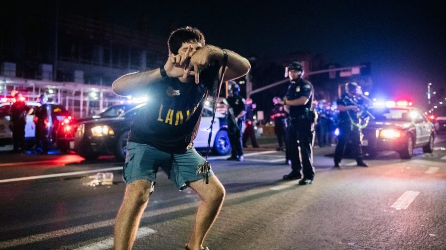 A Lakers fan celebrates in the streets of Los Angeles in front of many policemen.