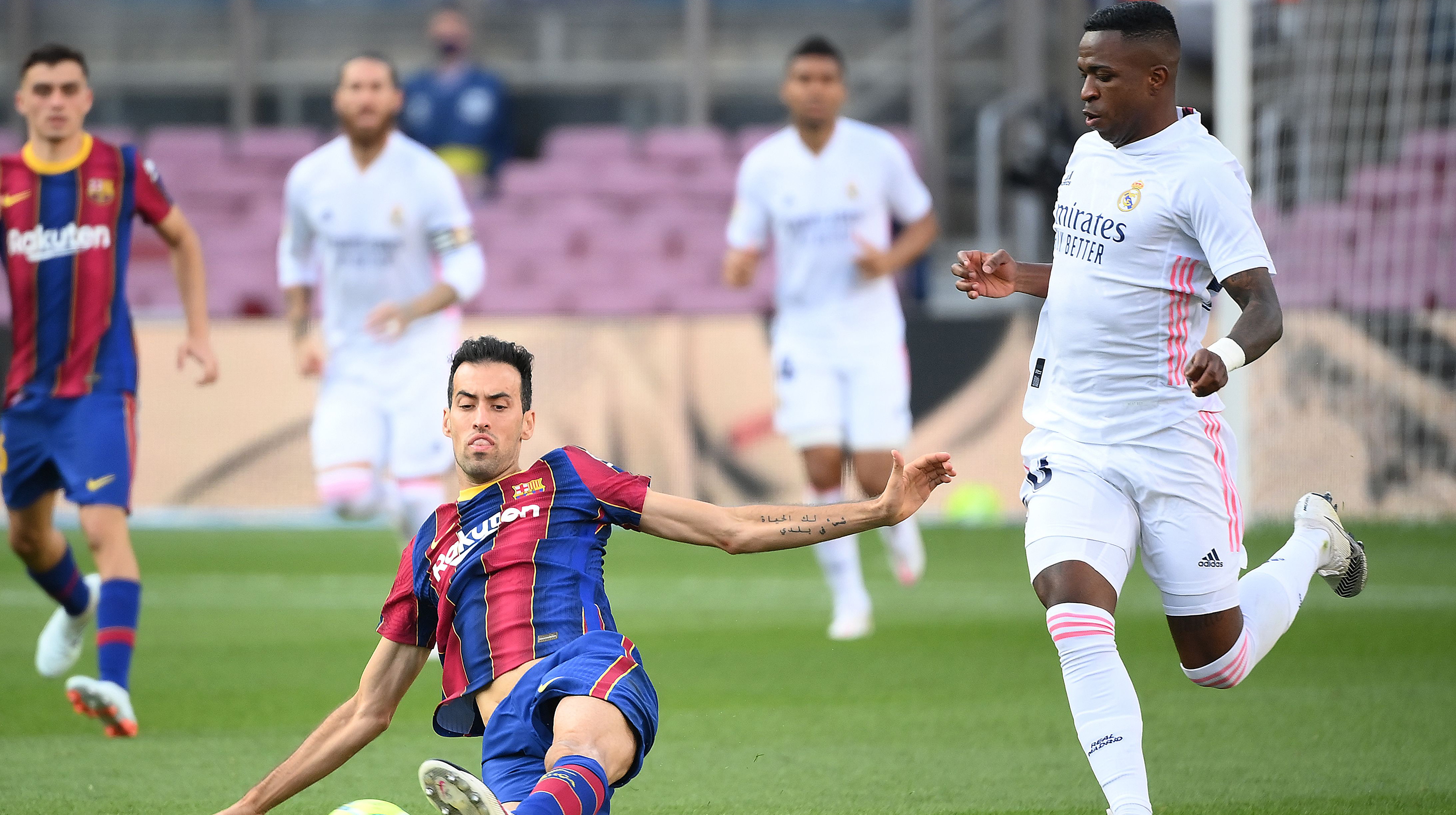 Real Madrid's Brazilian forward Vinicius Junior (R) challenges Barcelona's Spanish midfielder Sergio Busquets during the Spanish League football match between Barcelona and Real Madrid