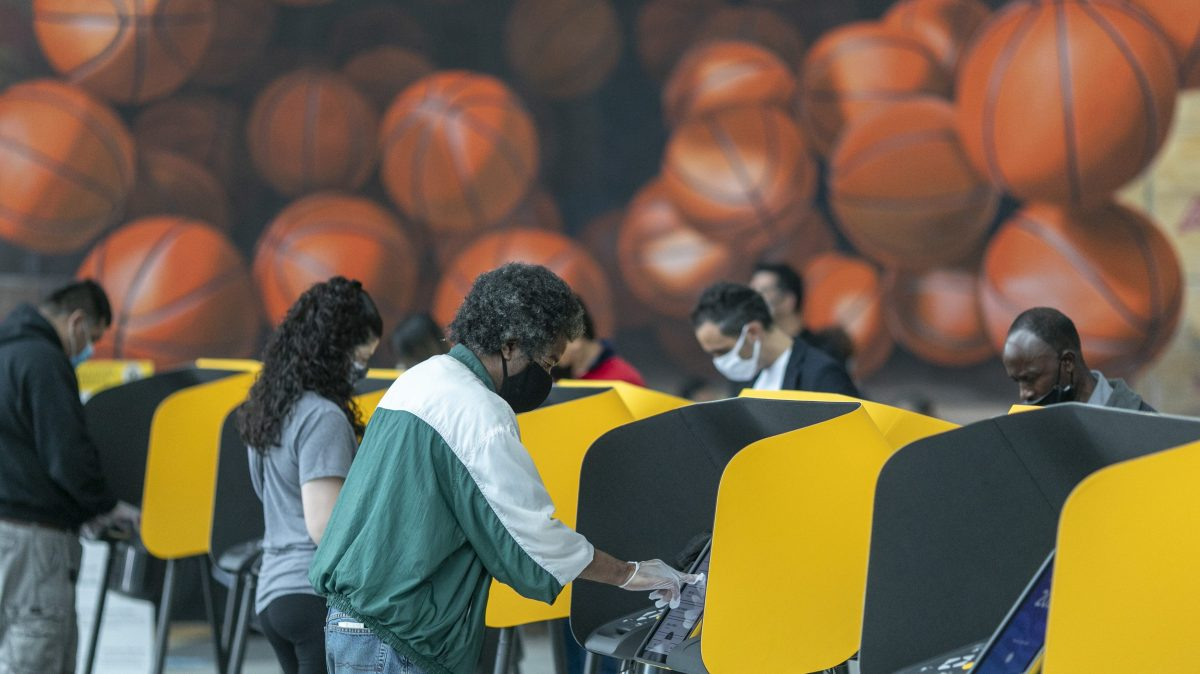 People cast their vote on the first day of early voting at the Vote Center at Staples Center sports and entertainment arena in Los Angeles, California
