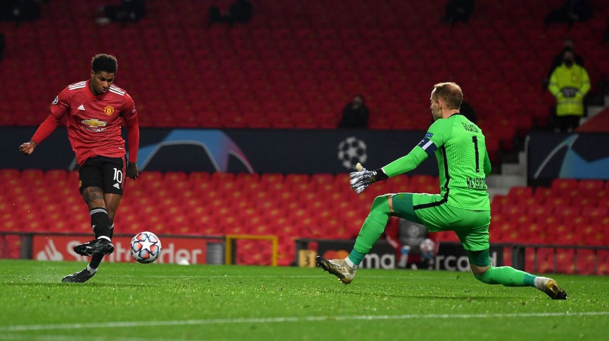 Manchester United's English striker Marcus Rashford (L) scores his team's second goal past RB Leipzig's Hungarian goalkeeper Peter Gulacsi during the UEFA Champions league group H football match between Manchester United and RB Leipzig at Old Trafford stadium in Manchester, north west England, on October 28, 2020.