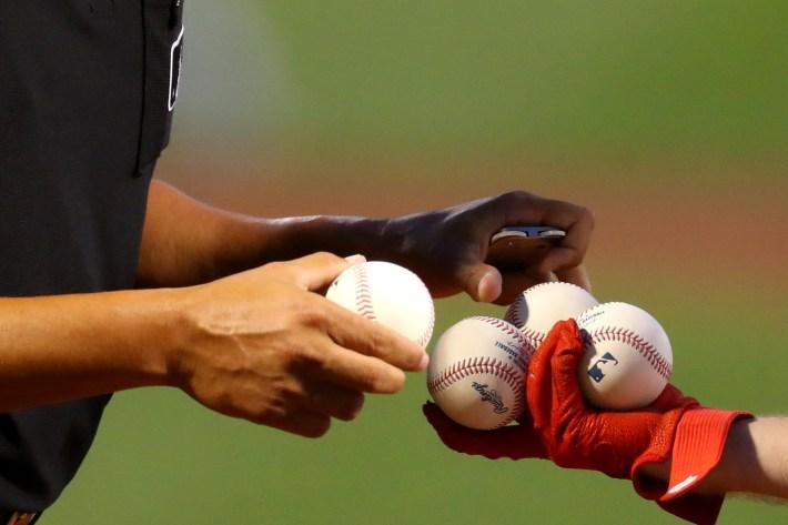 Baseball players handle some baseballs.