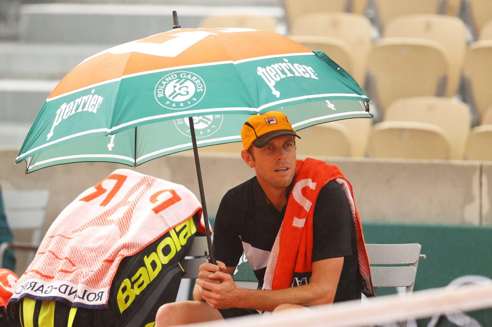 Sam Querrey sits under an umbrella at the French Open.