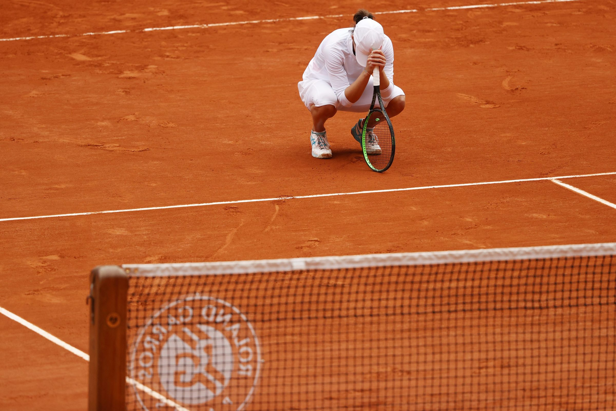 Iga Swiatek crouches to the court after winning the French Open.