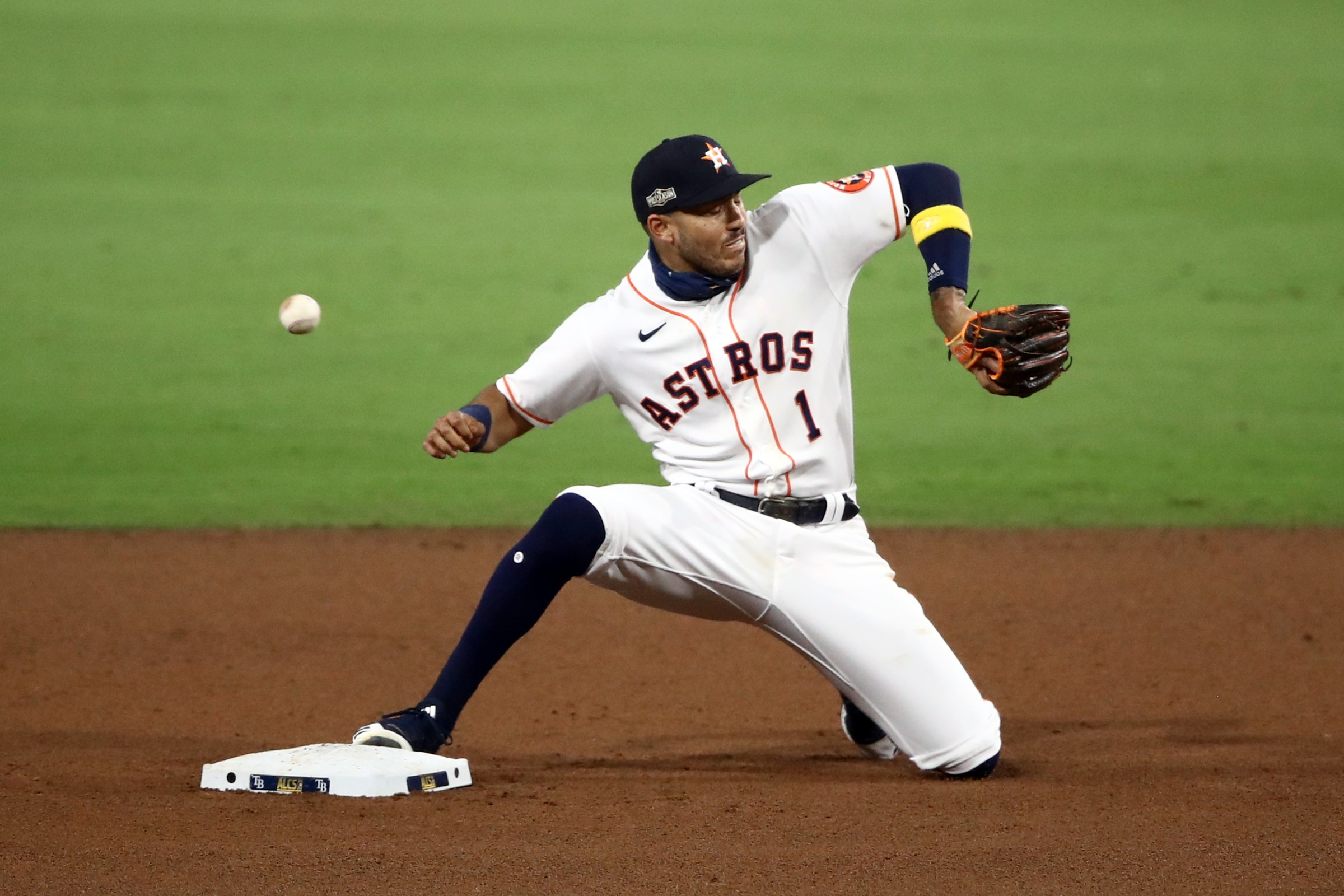 Carlos Correa #1 of the Houston Astros can't catch Jose Altuve's throw