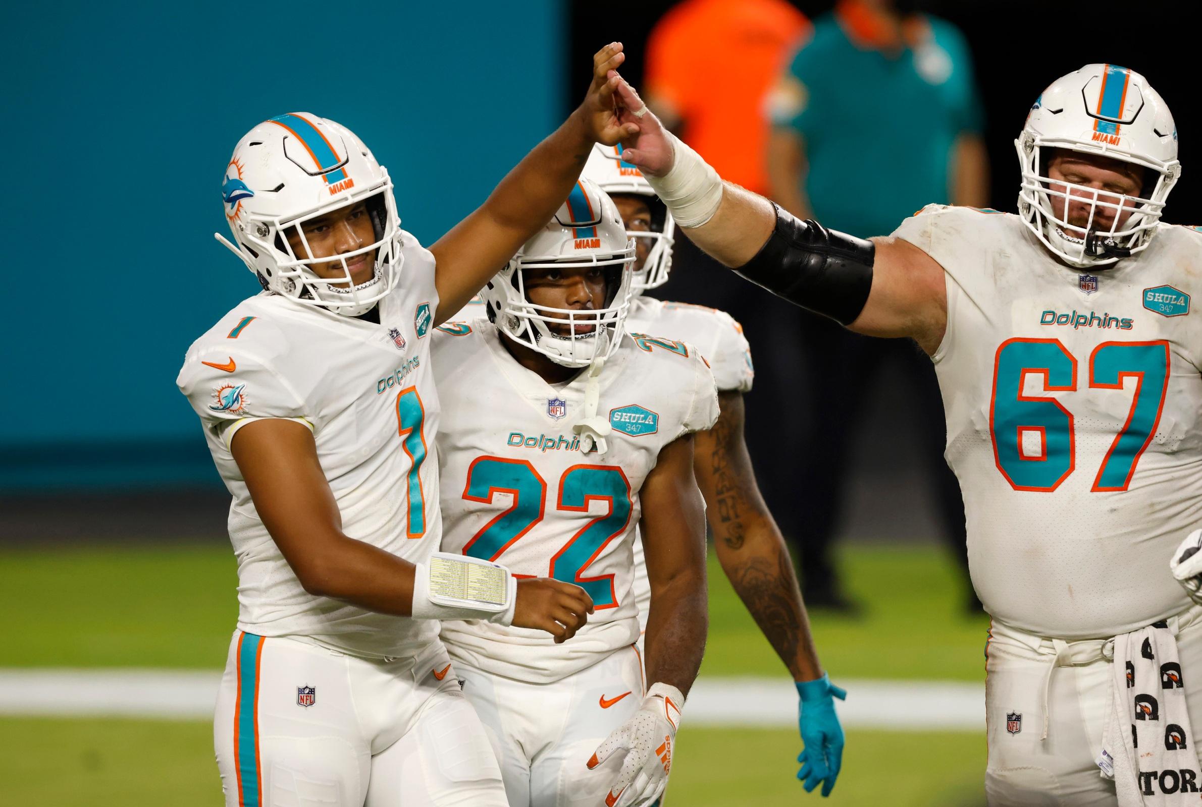 Quarterback Tua Tagovailoa #1 of the Miami Dolphins high fives teammate Ted Karras