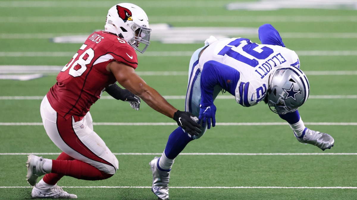 ARLINGTON, TEXAS - OCTOBER 19: Ezekiel Elliott #21 of the Dallas Cowboys is tackled by Jordan Hicks #58 of the Arizona Cardinals during the second quarter at AT&T Stadium on October 19, 2020, in Arlington, Texas. (Photo by Ronald Martinez/Getty Images)