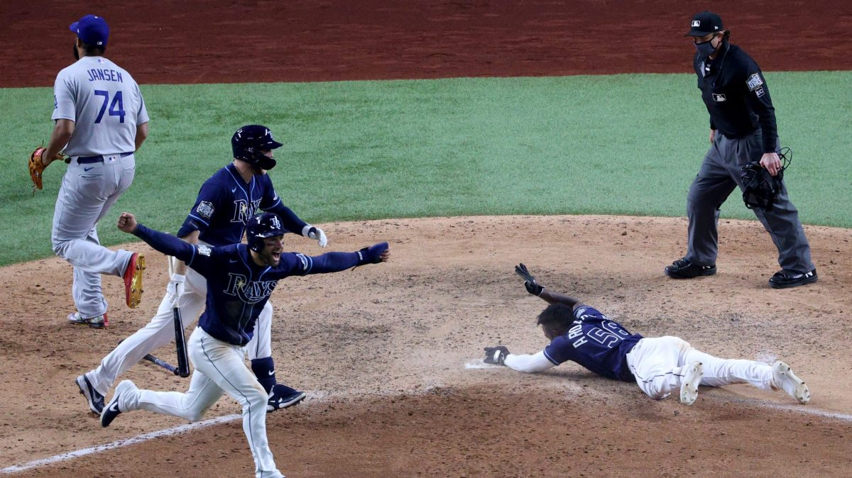 Randy Arozarena #56 of the Tampa Bay Rays slides into home plate during the ninth inning to score the game winning run to give his team the 8-7 victory as Kevin Kiermaier celebrates against the Los Angeles Dodgers in Game Four of the 2020 MLB World Series