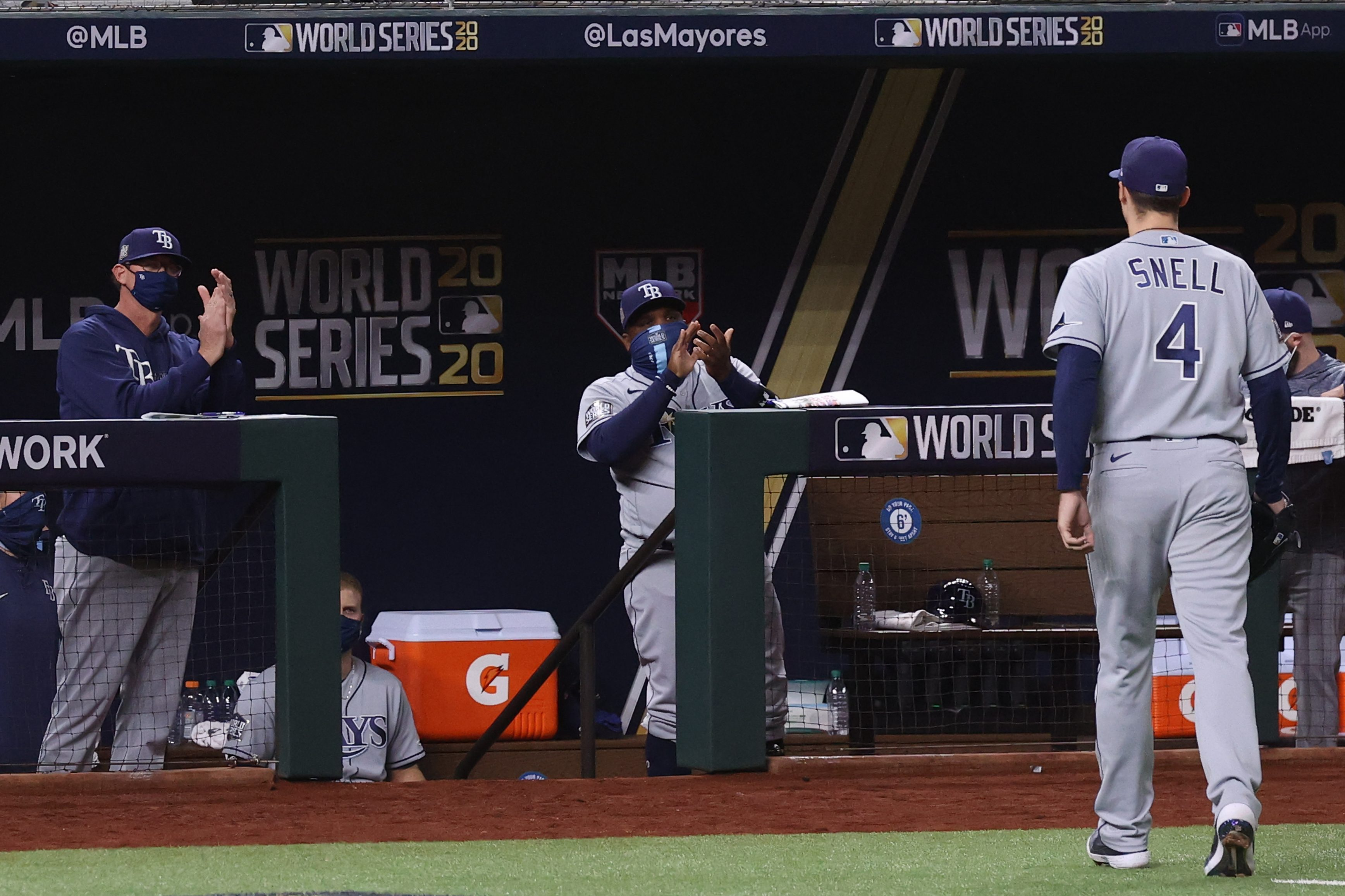 Blake Snell #4 of the Tampa Bay Rays is congratulated by pitching coach Kyle Snyder and third base coach Rodney Linares after being taken out of the game
