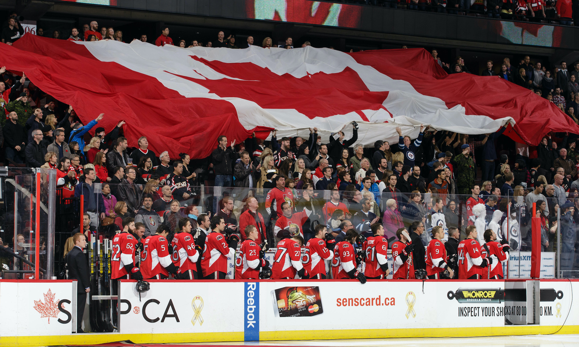 OTTAWA, ON - NOVEMBER 8: Members of the Ottawa Senators stand as a large Canadian flag is passed along in the stands during the singing of the national anthem prior to an NHL game against the Winnipeg Jets at Canadian Tire Centre on November 8, 2014 in Ottawa, Ontario, Canada. (Photo by Jana Chytilova/Freestyle Photography/Getty Images) *** Local Caption ***