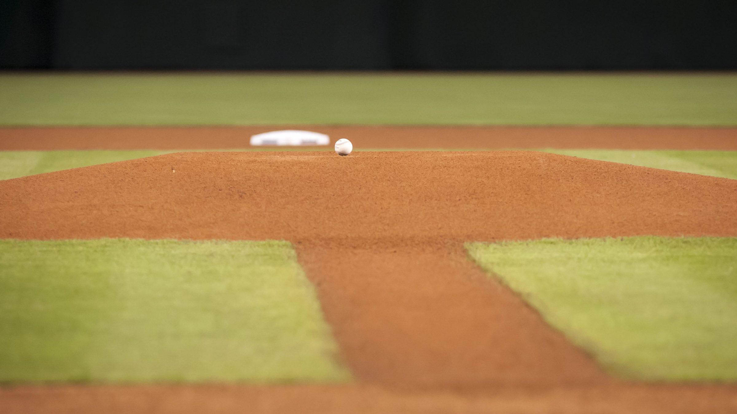 A baseball sitting on an empty baseball field.