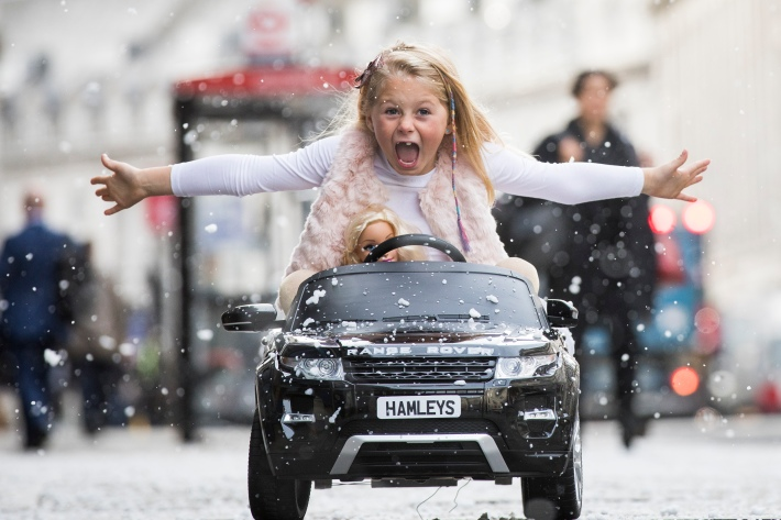 a young blonde girl rides with her arms out atop a toy car