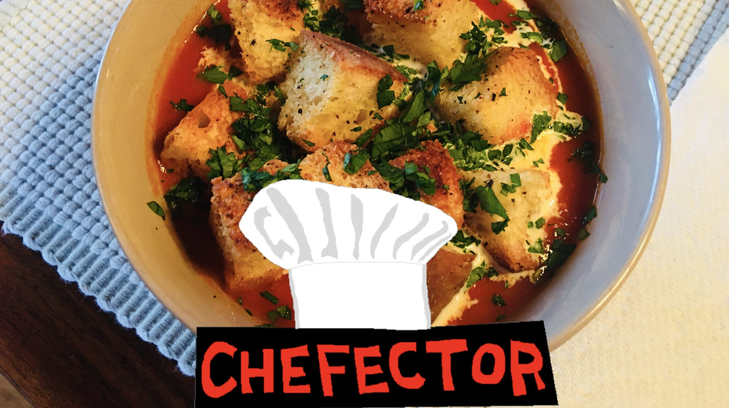 A bowl of tomato soup with croutons and herbs