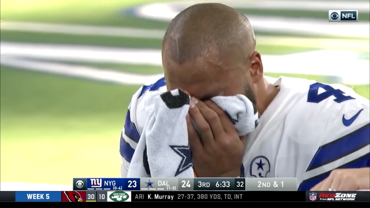 Dak Prescott covers his face with a towel as he leaves the field after his injury