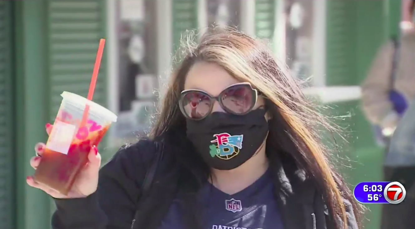 A woman holding a Dunkin' iced coffee and wearing a Patriots jersey and New England sports facemask