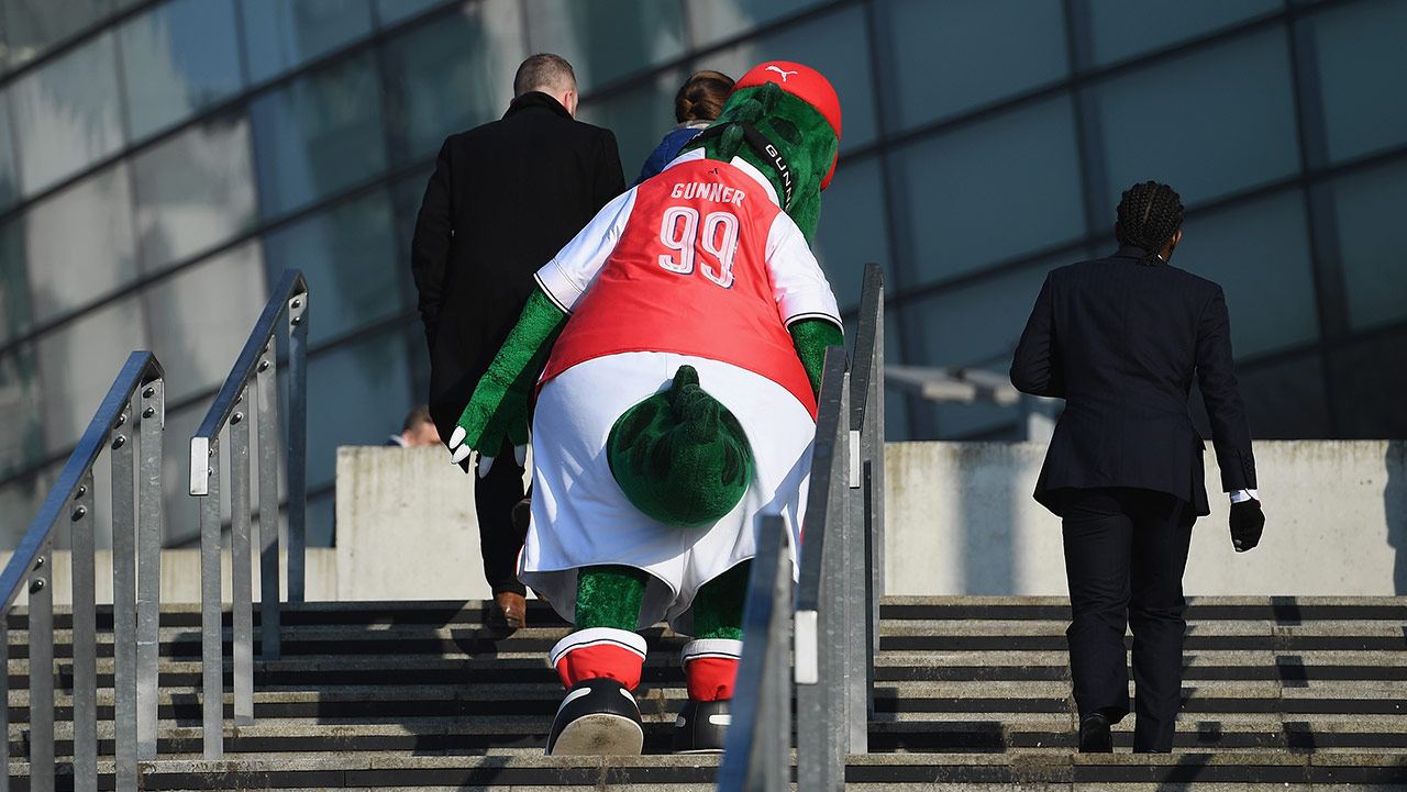 Gunnersaurus, the Arsenal mascot, which is a big green dinosaur in a red Arsenal jersey, walks up the steps escorted by some people in suits.