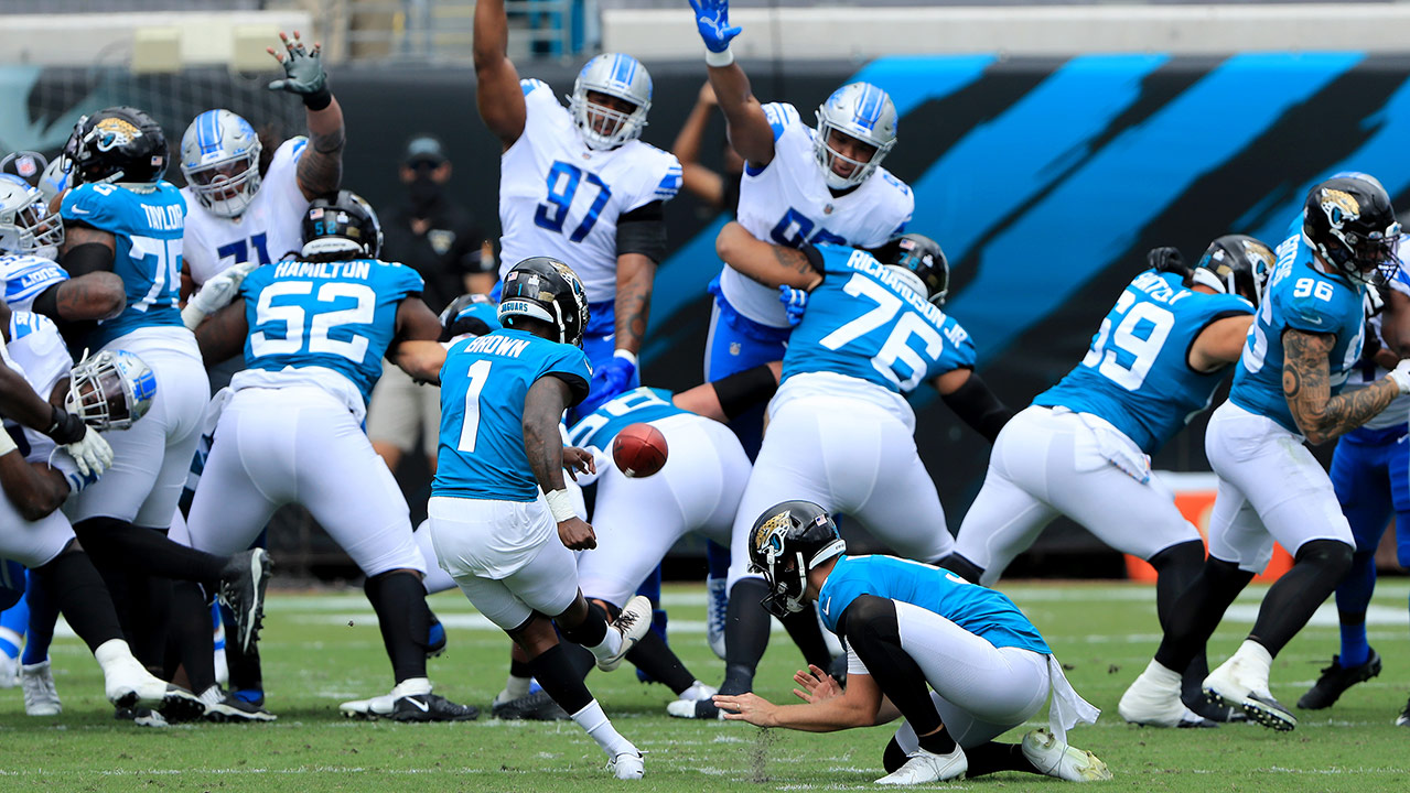 Jaguars kicker Jon Brown attempts a field goal. Lions players have their hands up to try to block it.