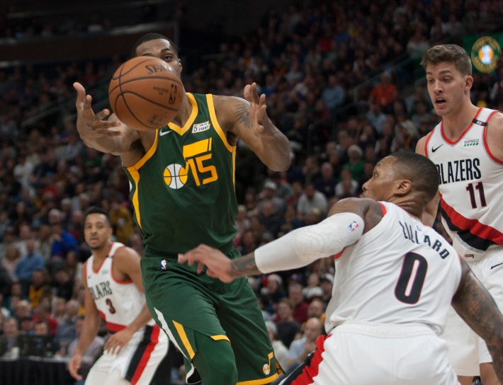 Derrick Favors of the Utah Jazz grabs a rebound as Damian Lillard, Meyers Leonard, and C.J. McCollum of the Portland Trail Blazers look on