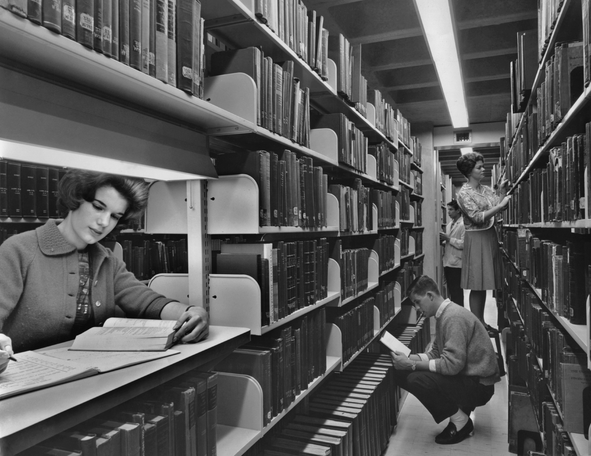 a few students read in a crowded library