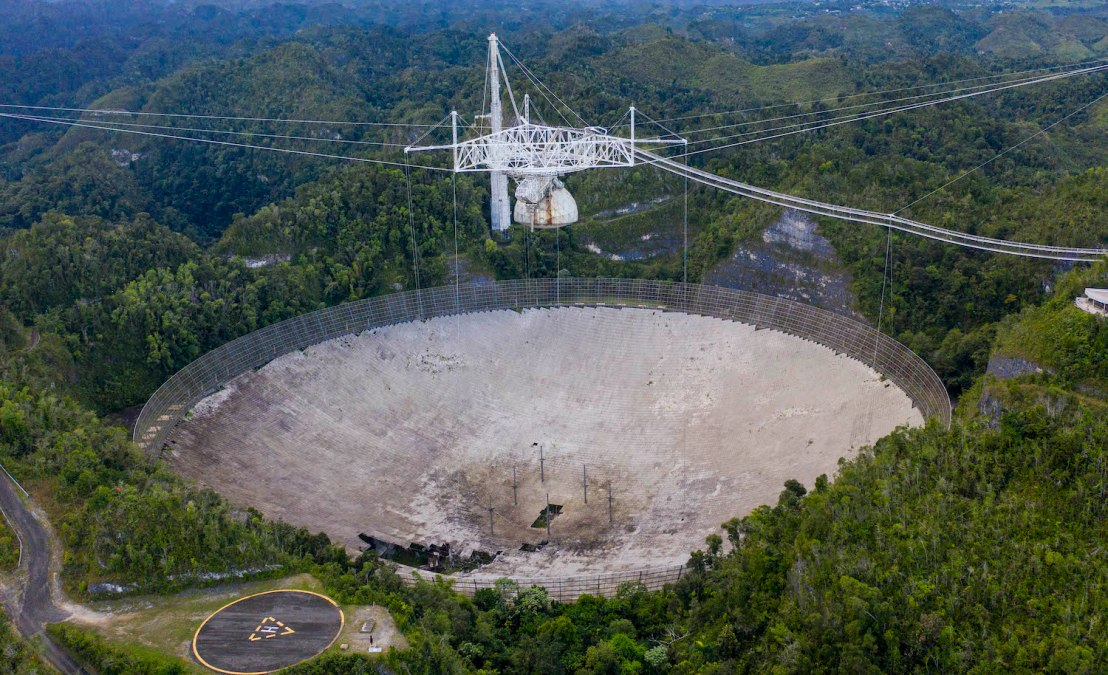 This aerial view shows a hole in the dish panels of the Arecibo Observatory in Arecibo, Puerto Rico, on November 19, 2020. - The National Science Foundation (NSF) announced on November 19, 2020, it will decommission the radio telescope following two cable breaks in recent months which have brought the structure to near collapse. (Photo by Ricardo ARDUENGO / AFP) (Photo by RICARDO ARDUENGO/AFP via Getty Images)