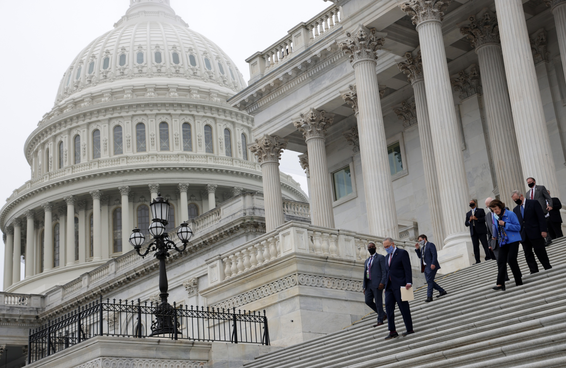Democratic members of U.S. Senate Judiciary Committee, led by Senate Minority Leader Sen. Chuck Schumer (D-NY), walk down the east front steps of the U.S. Capitol for a news conference after a boycott of the Senate Judiciary Committee hearing on the nomination of Judge Amy Coney Barrett to the U.S. Supreme Court on October 22, 2020 in Washington, DC.