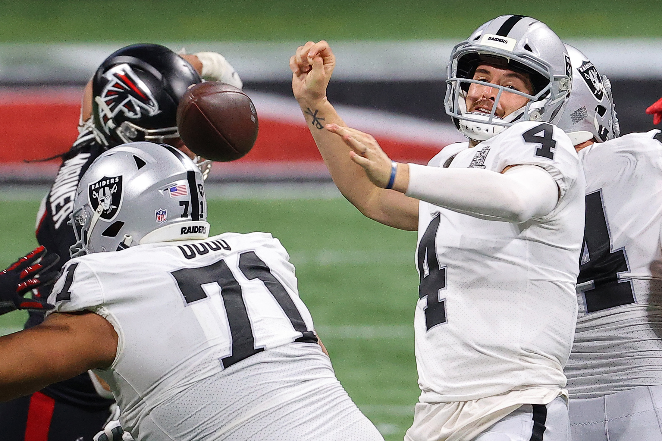 Derek Carr #4 of the Las Vegas Raiders is stripped of the ball during their NFL game against the Atlanta Falcons at Mercedes-Benz Stadium on November 29, 2020 in Atlanta, Georgia.