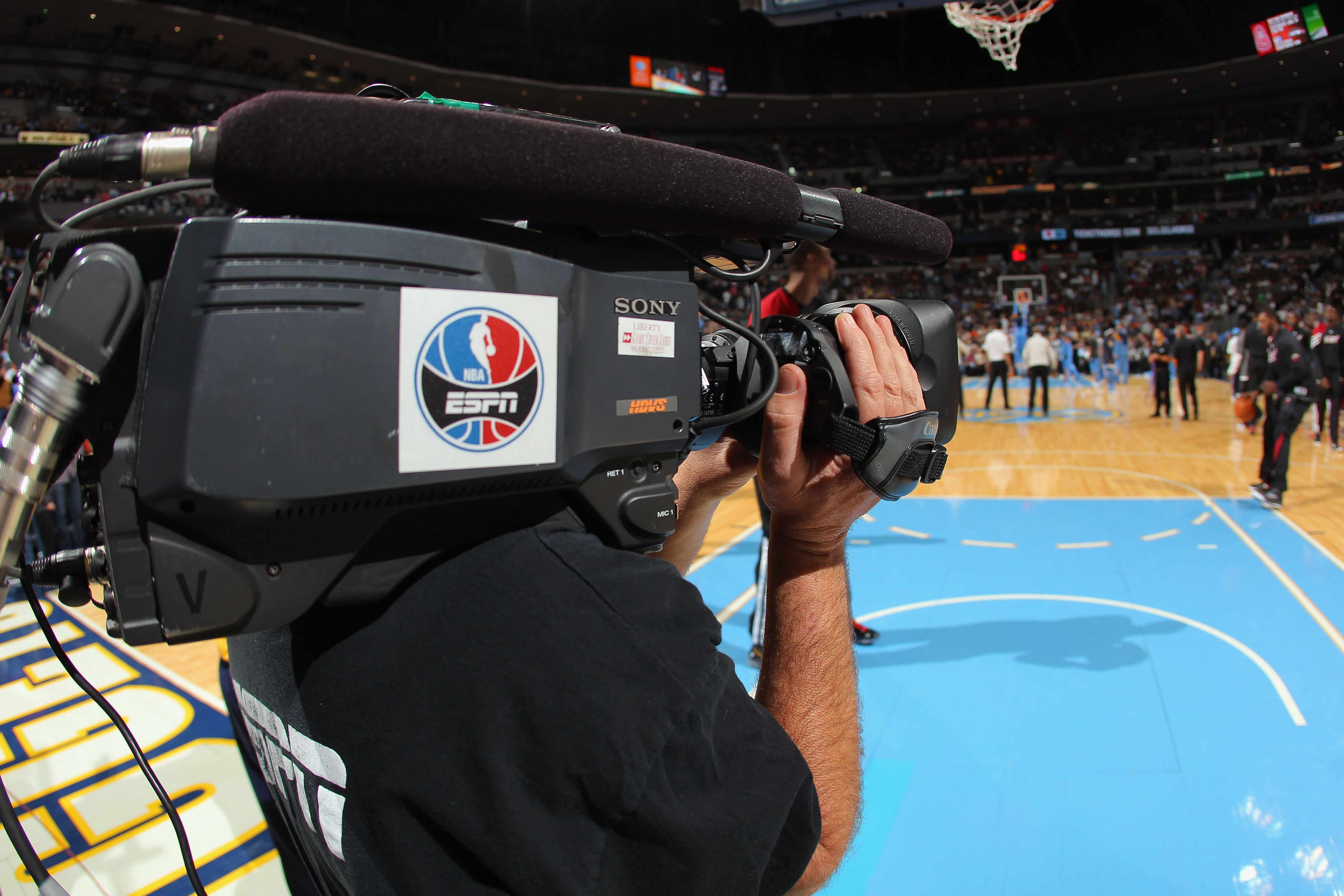 an ESPN cameraman stands in front of a basketball court