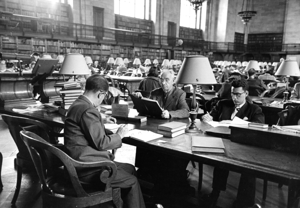 Three men share a table as they read in the South Reading Room at the main branch of the New York Public Library in New York City, New York, 1953.