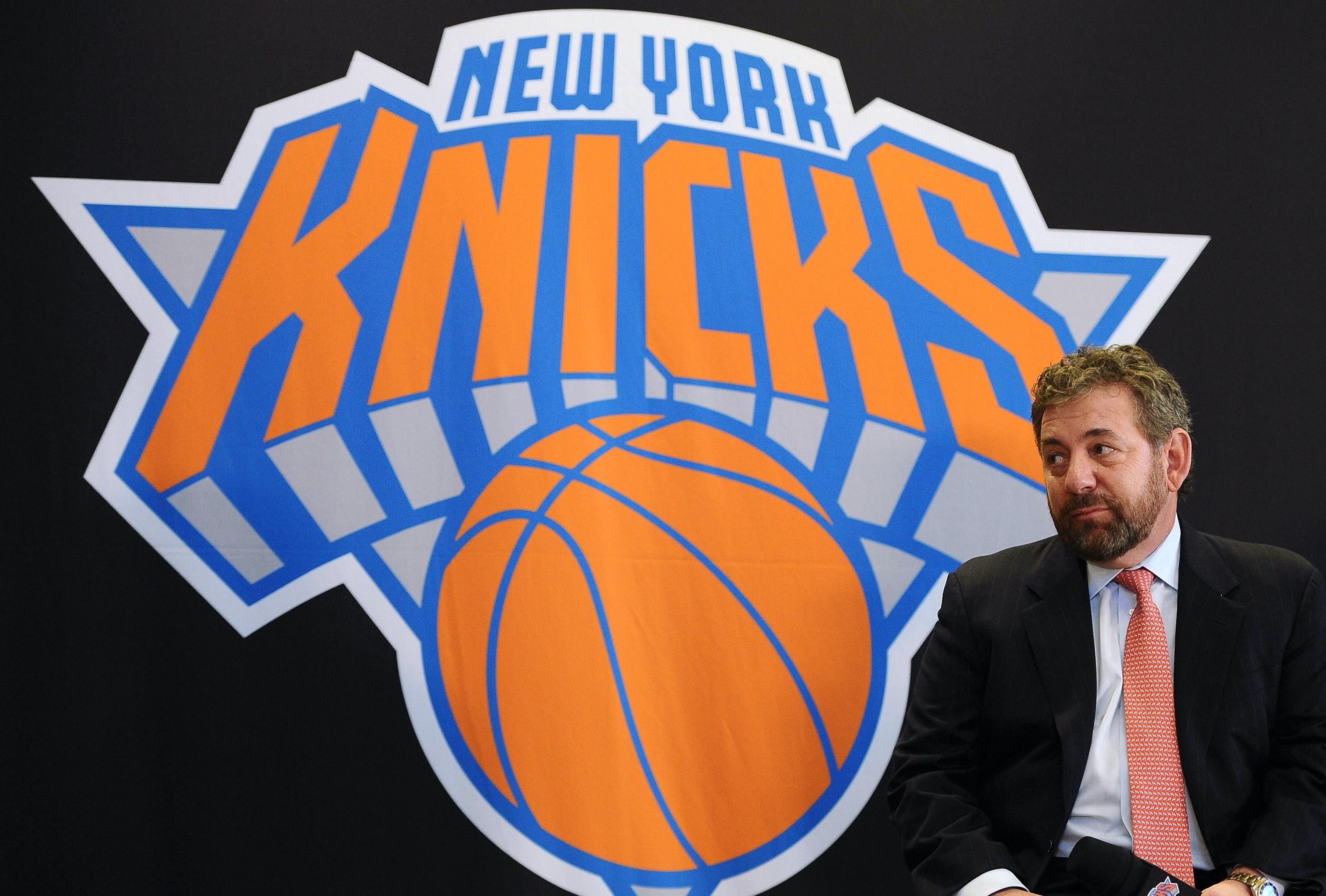 James Dolan sits next to a big Knicks logo.