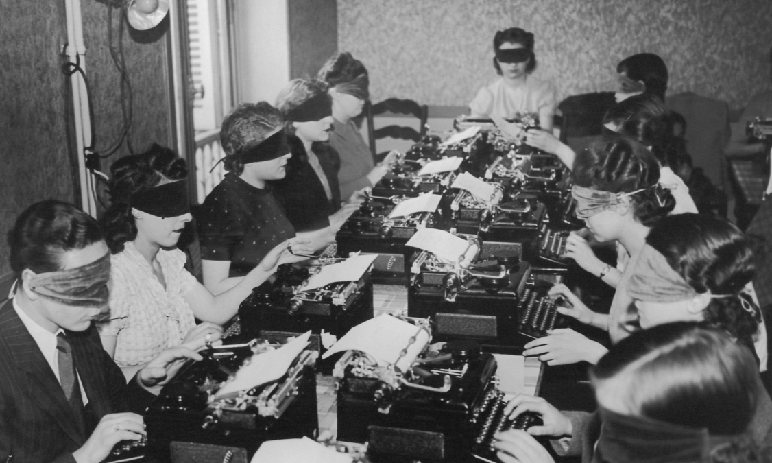Some old-timey types type at typewriters while blindfolded.
