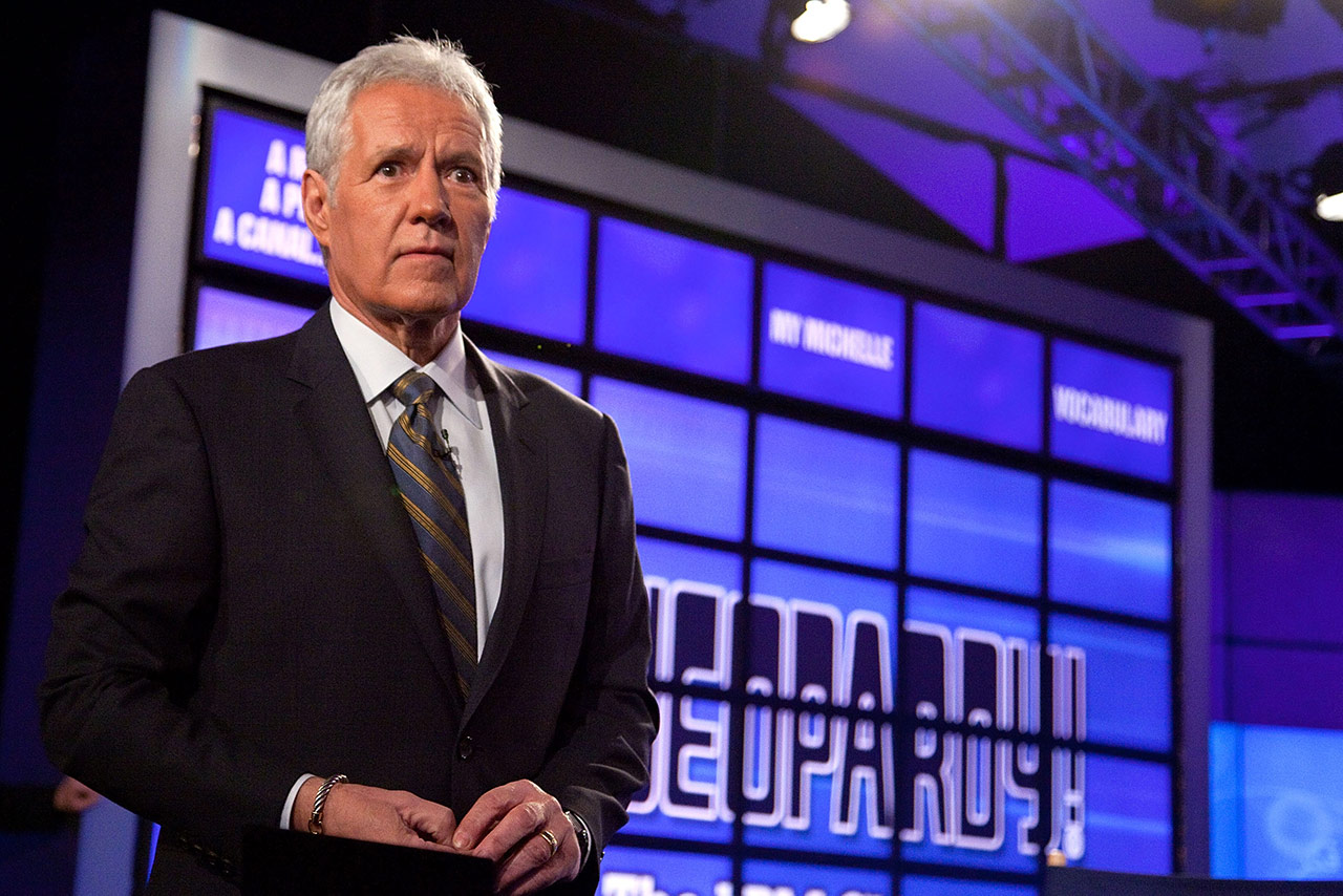 Alex Trebek stands in front of a Jeopardy! board