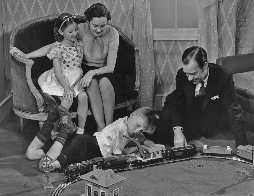 Father and son play with a toy train set as mother and daughter look on circa 1940's.