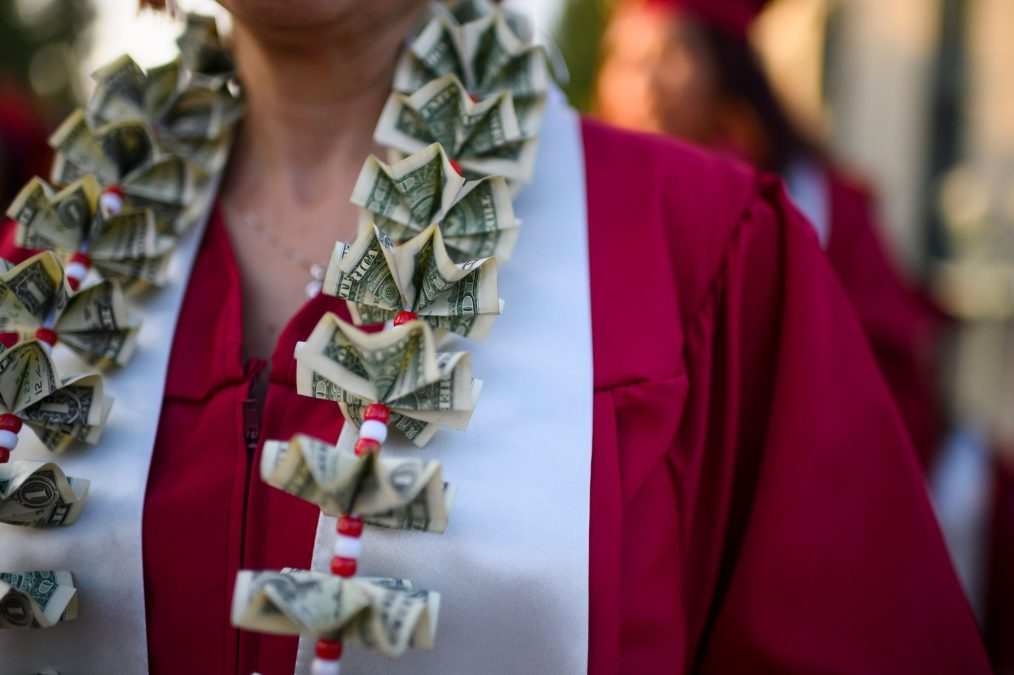 """A graduating student wears a money lei, a necklace made of US dollar bills, at the Pasadena City College graduation ceremony, June 14, 2019, in Pasadena, California. - With 45 million borrowers owing $1.5 trillion, the student debt crisis in the United States has exploded in recent years and has become a key electoral issue in the run-up to the 2020 presidential elections. """"Somebody who graduates from a public university this year is expected to have over $35,000 in student loan debt on average,"""" said Cody Hounanian, program director of Student Debt Crisis, a California NGO that assists students and is fighting for reforms."""