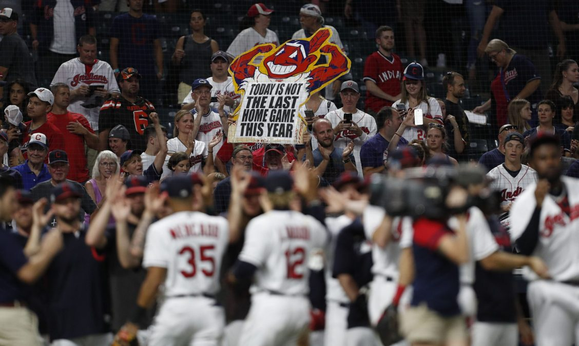 Fans hold up a Chief Wahoo sign at a Cleveland baseball game.